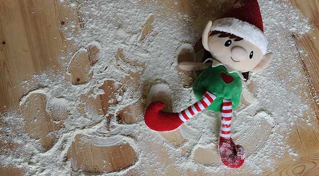 Christmas Elf Making Snow Angels in Flour